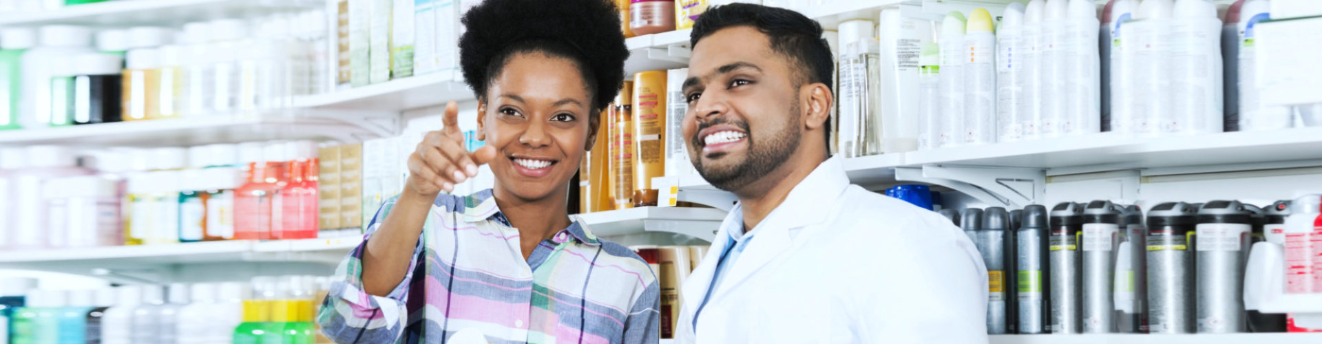 photo of a customer pointing at something while pharmacist looking at it smiling
